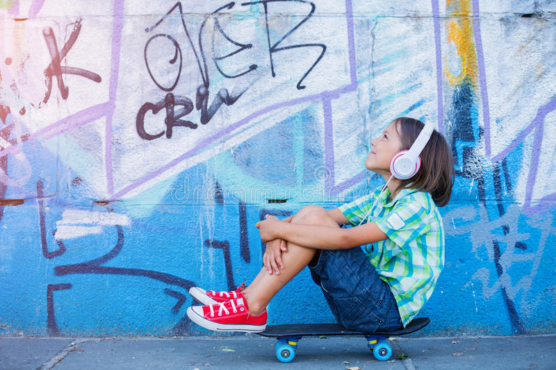 Cute boy with skateboard outdoors, standing on the street with different colorful graffiti on the walls stock image