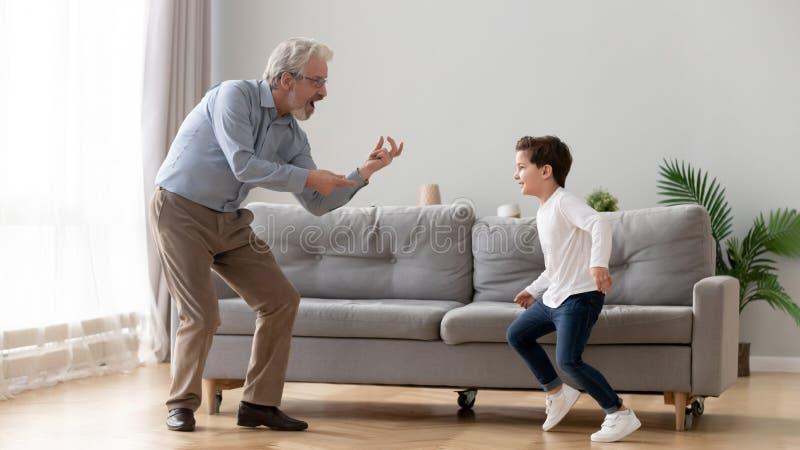 Cute boy sonson som dansar med gammal farfar i vardagsrummet royaltyfria bilder