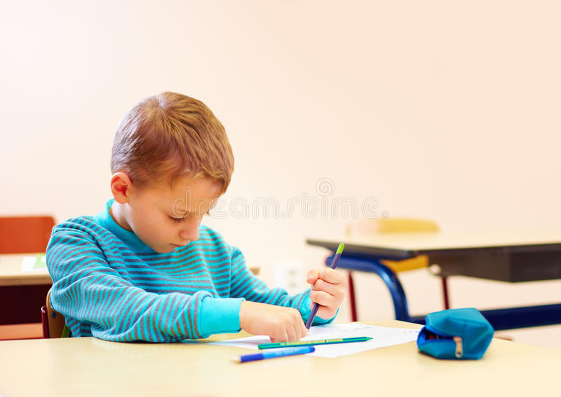 Cute boy with special needs writing letters while sitting at the desk in class room. Cute kid boy with special needs writing letters while sitting at the desk in stock image