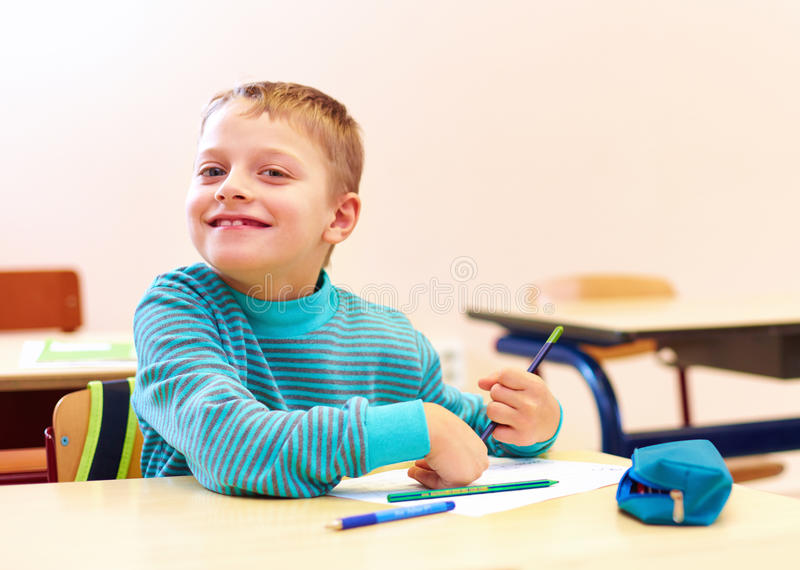 Cute boy with special needs writing letters while sitting at the desk in class room. Cute kid boy with special needs writing letters while sitting at the desk in stock photo