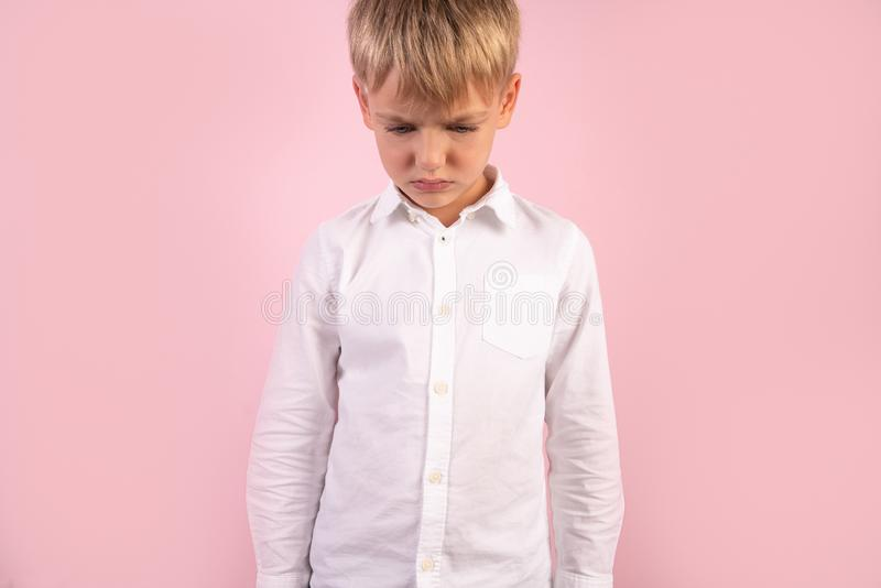 A cute boy stands next to pink wall, whites hirt, hands in pockets, bowing his head down.  stock images