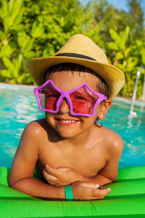 Cute boy in star-shaped sunglasses on green airbed. In the swimming pool outside in summer royalty free stock photography