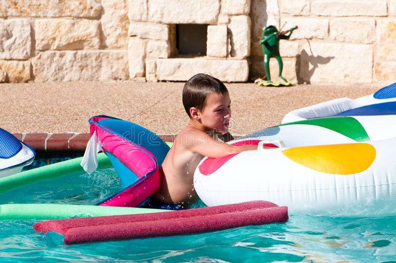Cute boy swimming on rafts stock photography