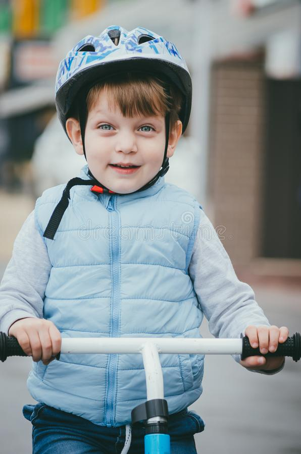 Cute boy of three years old in a blue vest and protective helmet rides a bike run along a city street. Children`s useful games in. The fresh air. Fun sport stock image