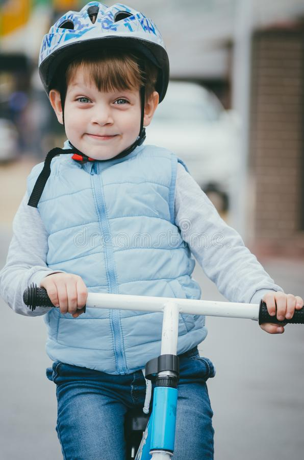 Cute boy of three years old in a blue vest and protective helmet rides a bike run along a city street. Children`s useful games in. The fresh air. Fun sport stock photography