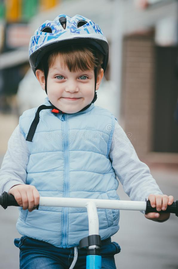 Cute boy of three years old in a blue vest and protective helmet rides a bike run along a city street. Children`s useful games in. The fresh air. Fun sport royalty free stock image
