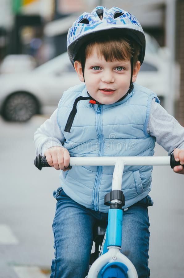 Cute boy of three years old in a blue vest and protective helmet rides a bike run along a city street. Children`s useful games in. The fresh air. Fun sport royalty free stock images