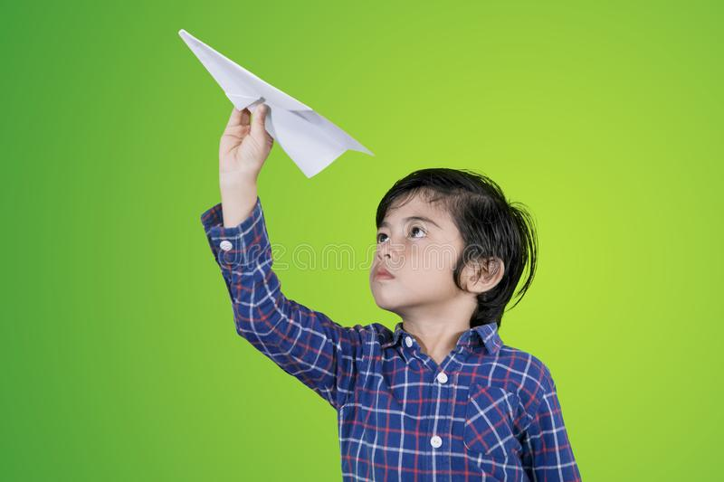 Cute boy throwing a paper plane. Picture of a cute little boy throwing a paper plane while playing in the studio with green screen background royalty free stock photo