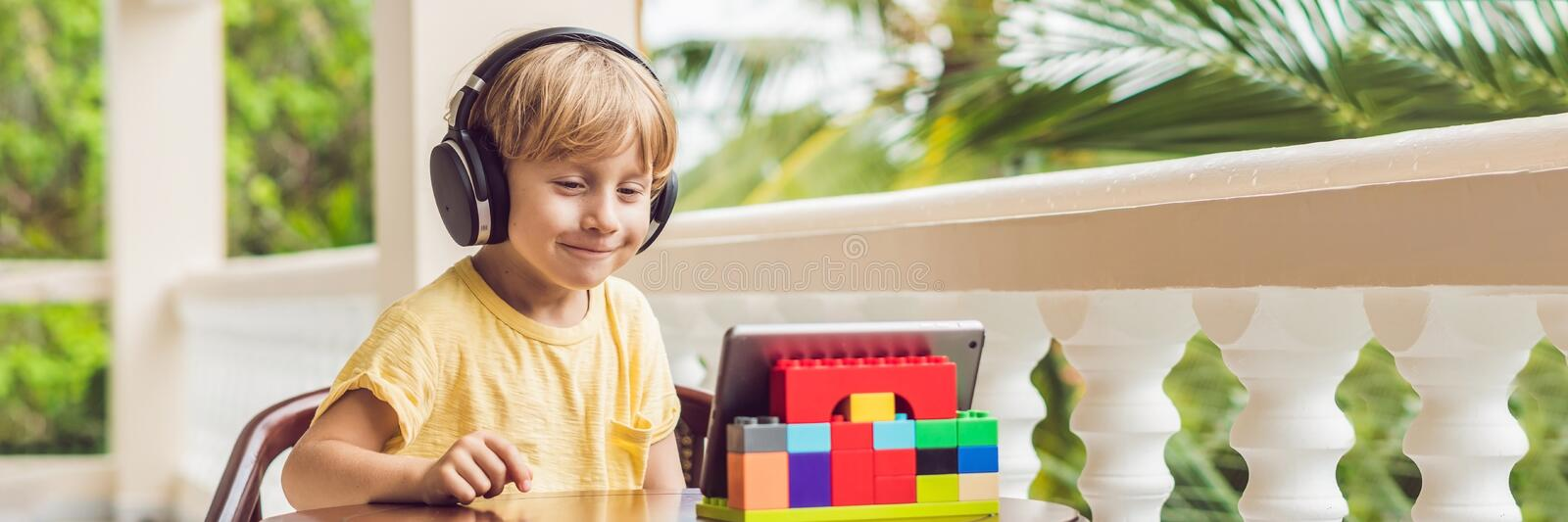 Boy in tropics talking with friends and family on video call using a tablet and wireless headphones BANNER, long format. Cute boy in the tropics talking with stock photos