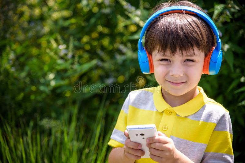 Cute boy using earphone to listening song outdoor with his happy face. Mixed race child having fun while using USB player to stock photos