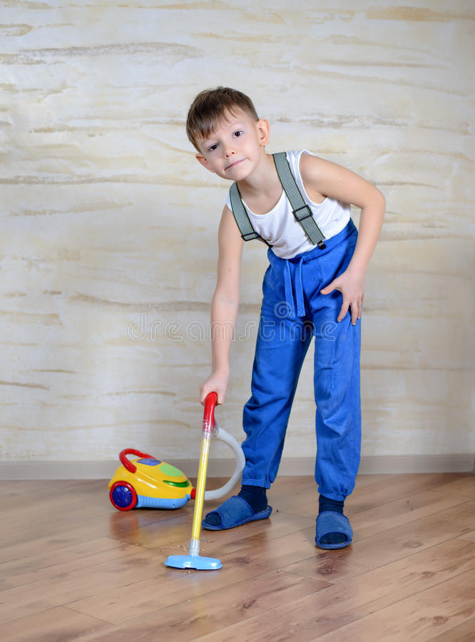 Cute boy using toy vaccuum stock photo