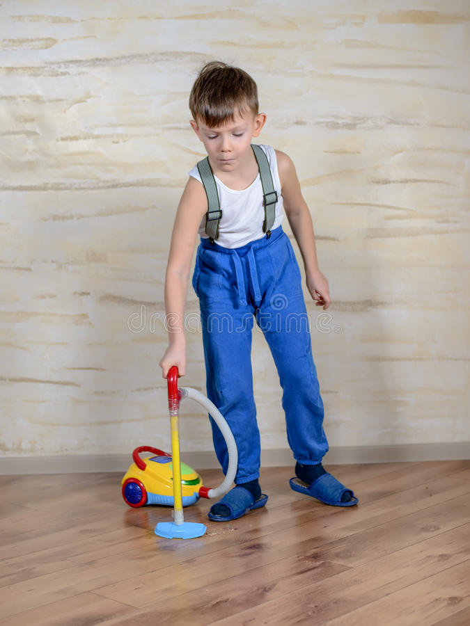 Cute boy using toy vaccuum royalty free stock photography