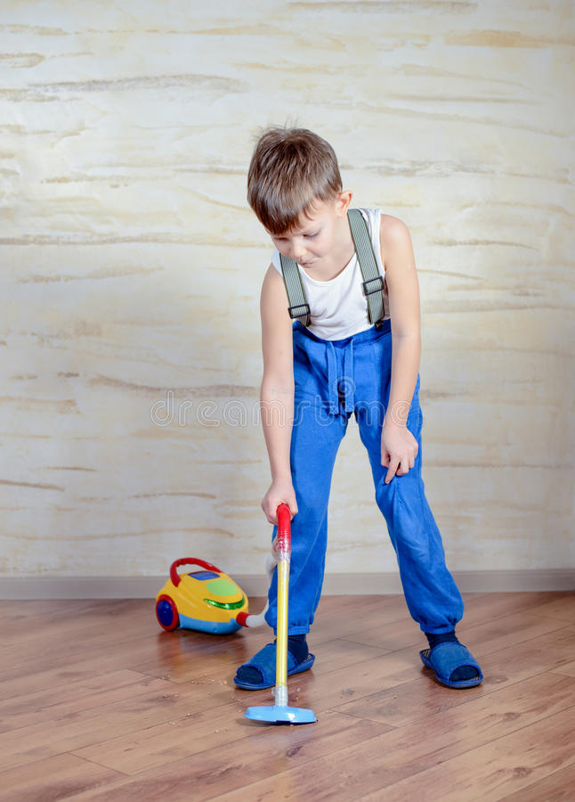 Cute boy using toy vaccuum royalty free stock photos