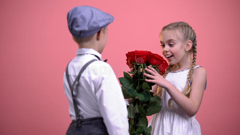 Cute boy in vintage clothes gifting roses to young beautiful girl, first love stock photo