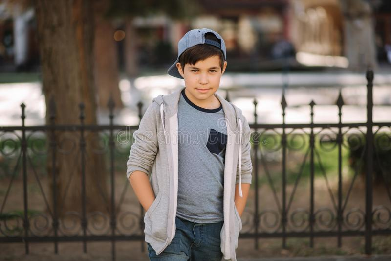 Cute boy walking in the city. Stylish teenage boy outside royalty free stock photography