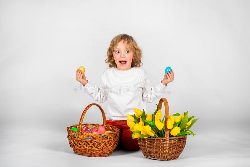 Cute boy with wavy hair sits on a white background next to a basket with Easter eggs stock images