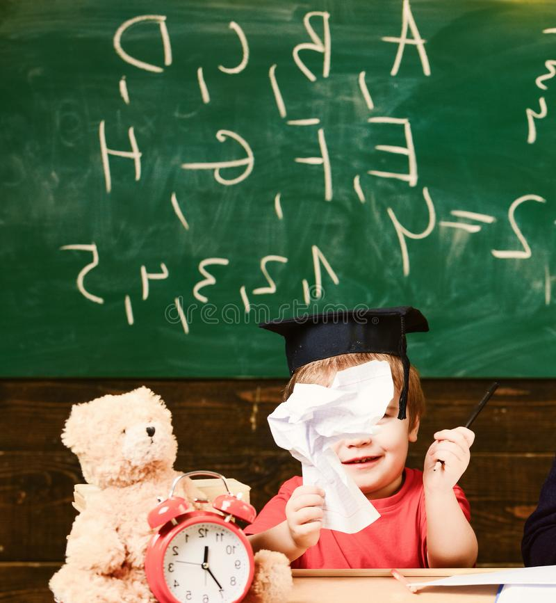 Cute boy wearing academic cap in the classroom. Little child holding paper figure. Smiling kid sitting at the desk in royalty free stock image
