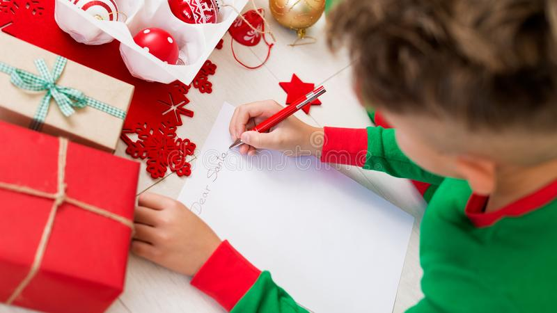 Cute boy wearing christmas pajamas writing letter to Santa on livingroom floor. Overhead view of a young boy writing wishlist. stock photos