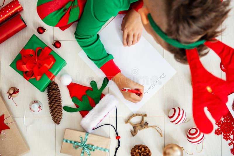 Cute boy wearing christmas pajamas writing letter to Santa on livingroom floor. Overhead view of a young boy writing wish list. royalty free stock image