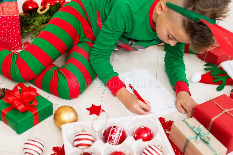 Cute boy wearing christmas pajamas writing letter to Santa on livingroom floor. Overhead view of a young boy writing wishlist. stock photo