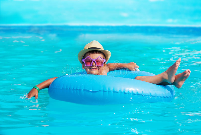 Cute boy wearing hat, glasses in inflatable ring. Cute boy wearing hat and glasses in inflatable ring swimming in pool outside during summer sunny day stock photo