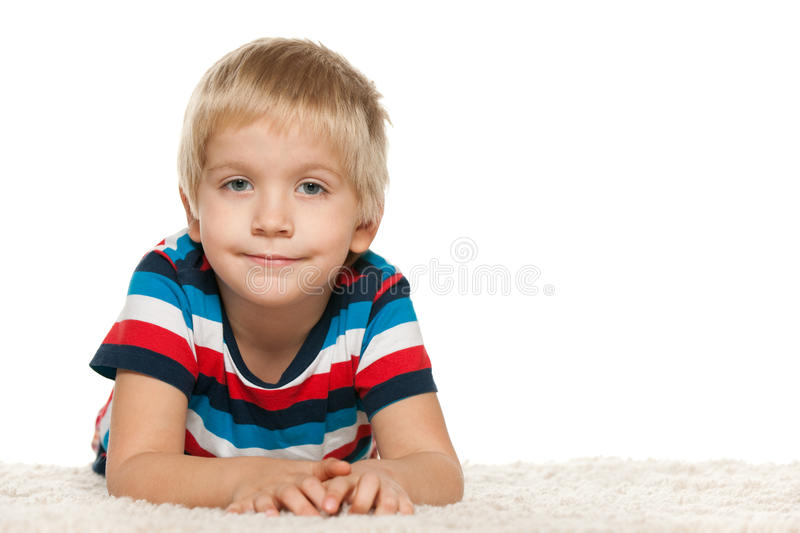 Cute boy on the white carpet royalty free stock images