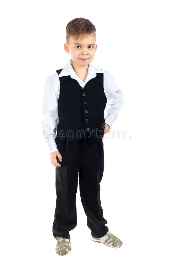 A cute boy in a white shirt, vest and trousers royalty free stock photos