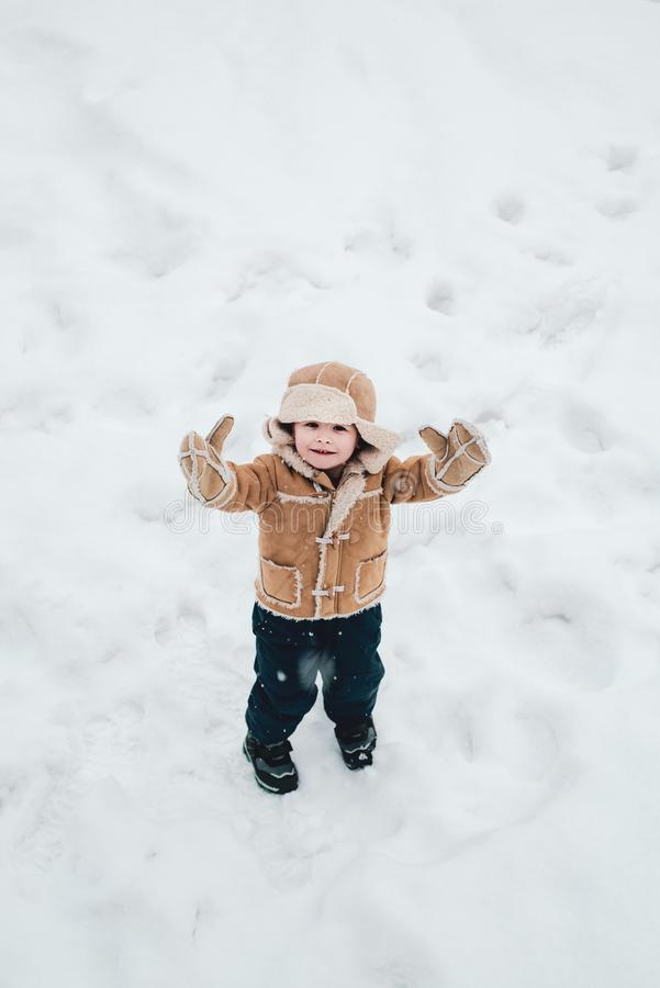 Cute boy in winter clothes. Making snowball and winter fun for children. Happy child playing with snow on a snowy winter stock photography