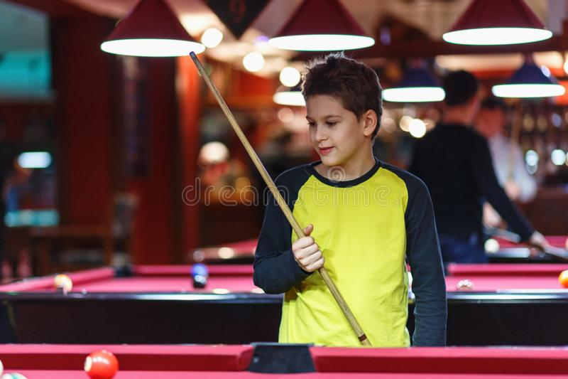 Cute boy in yellow t shirt plays billiard or pool in club. Young Kid learns to play snooker. Boy with billiard cue royalty free stock image