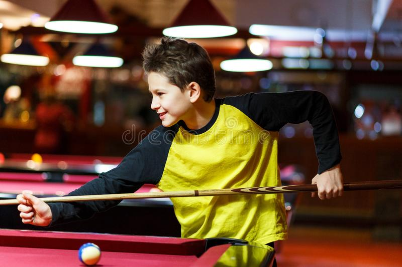 Cute boy in yellow t shirt plays billiard or pool in club. Young Kid learns to play snooker. Boy with billiard cue royalty free stock images