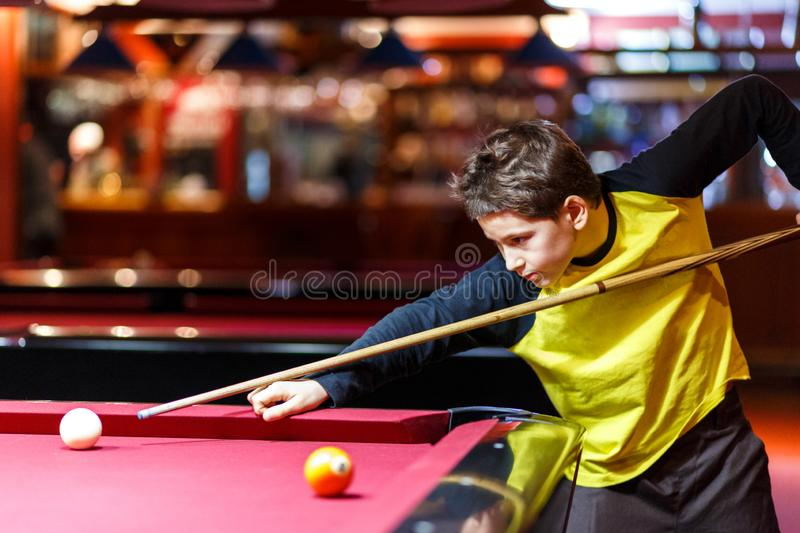 Cute boy in yellow t shirt plays billiard or pool in club. Young Kid learns to play snooker. Boy with billiard cue stock images