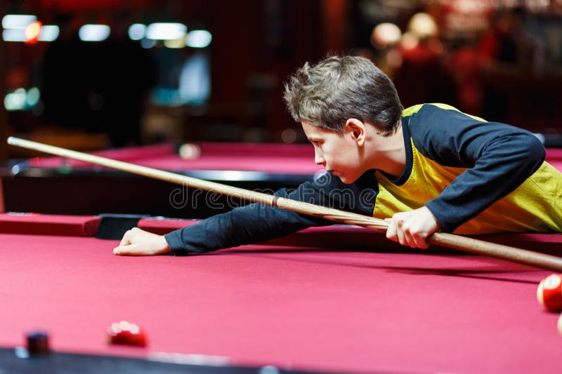 Cute boy in yellow t shirt plays billiard or pool in club. Young Kid learns to play snooker. Boy with billiard cue royalty free stock photography