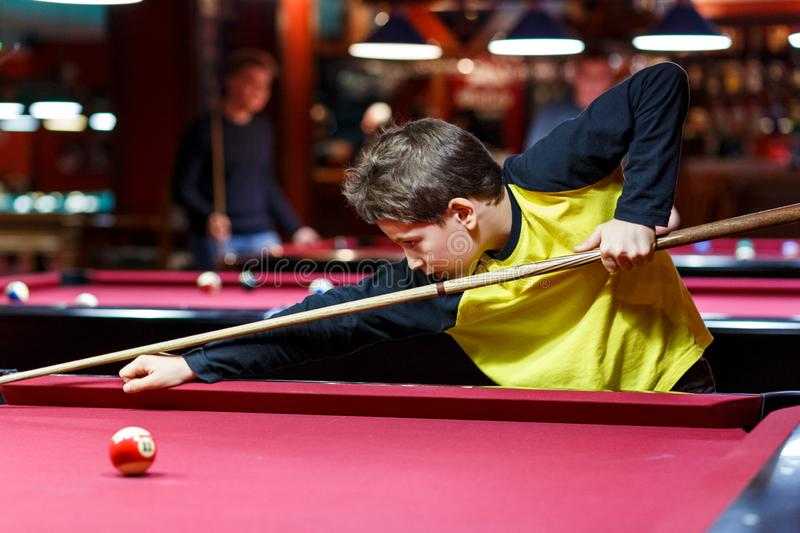 Cute boy in yellow t shirt plays billiard or pool in club. Young Kid learns to play snooker. Boy with billiard cue royalty free stock photos