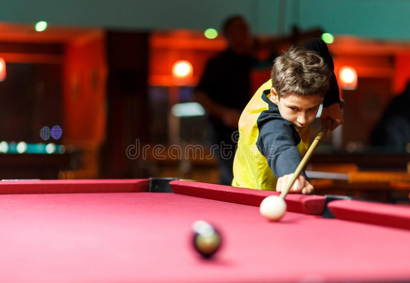 Cute boy in yellow t shirt plays billiard or pool in club. Young Kid learns to play snooker. Boy with billiard cue stock image
