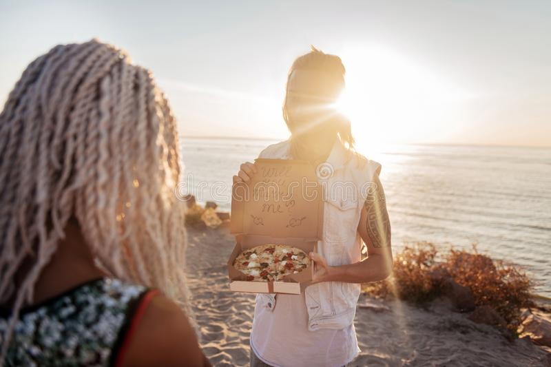 Cute boyfriend opening box with pizza asking his woman to marry him stock photo