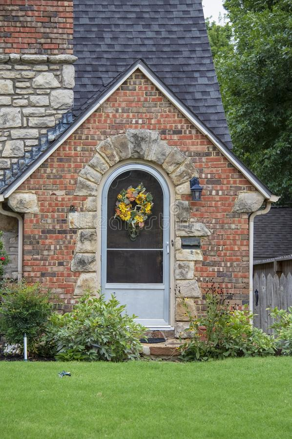 Cute brick and rock cottage with gabled entrance and arched door with bright green lawn and fall wreath on door. royalty free stock photos