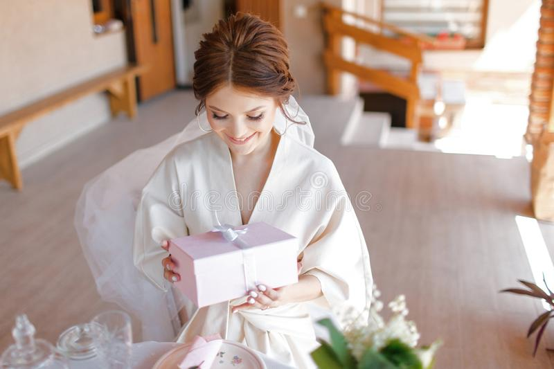 The cute bride is sitting on the terrace and with a smile unwrapping a present stock photography