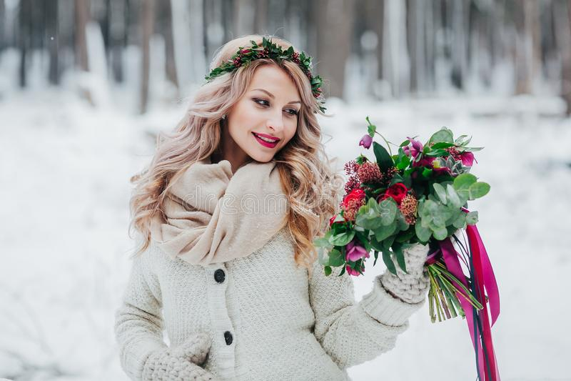 Cute bride of Slavic appearance with a wreath of wildflowers holds a bouquet winter background. Winter wedding royalty free stock image