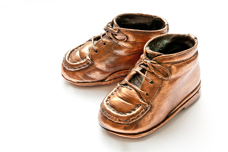Cute bronze babyshoes. Babyshoes in bronze, on white background stock image