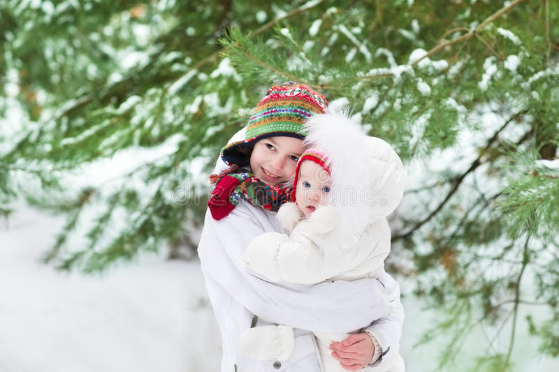 Cute brother and his baby sister in snowy park. Cute boy hugging his baby sister in a beautiful winter park under big tree royalty free stock images