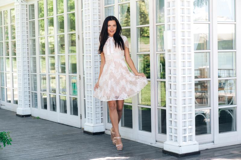 Cute brunette with beautiful long legs posing in beige colour dress outside near a wooden and glass wall stock image