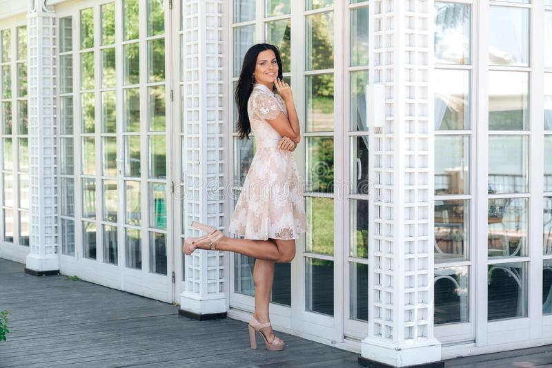 Cute brunette with beautiful long legs posing in beige colour dress outside near a wooden and glass wall stock photography