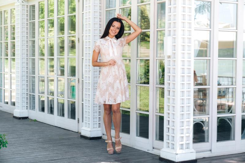 Cute brunette with beautiful long legs posing in beige colour dress outside near a wooden and glass wall royalty free stock photos