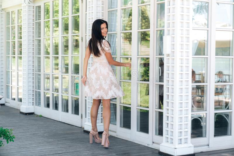 Cute brunette with beautiful long legs posing in beige colour dress outside near a wooden and glass wall stock photo