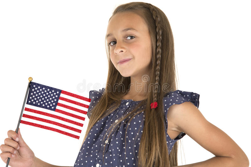 Cute brunette girl holding an American flag smiling. Cute brunette holding an American flag smiling royalty free stock photos