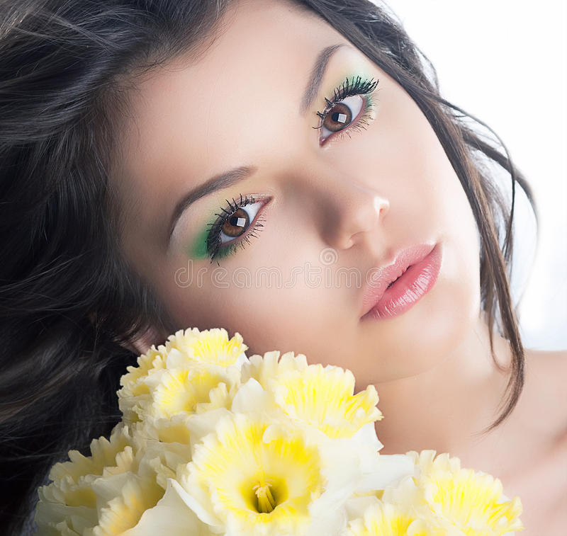 Cute brunette girl with narcissus stock images