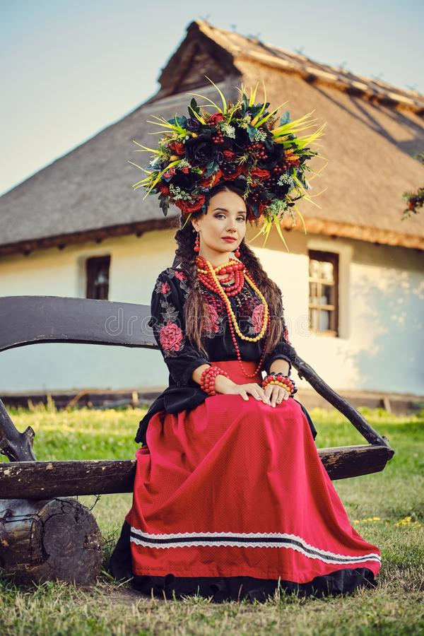 Brunette girl in a white ukrainian authentic national costume and a wreath of flowers is posing sitting on a wooden. Cute brunette lady with a long dark hair, in stock photography