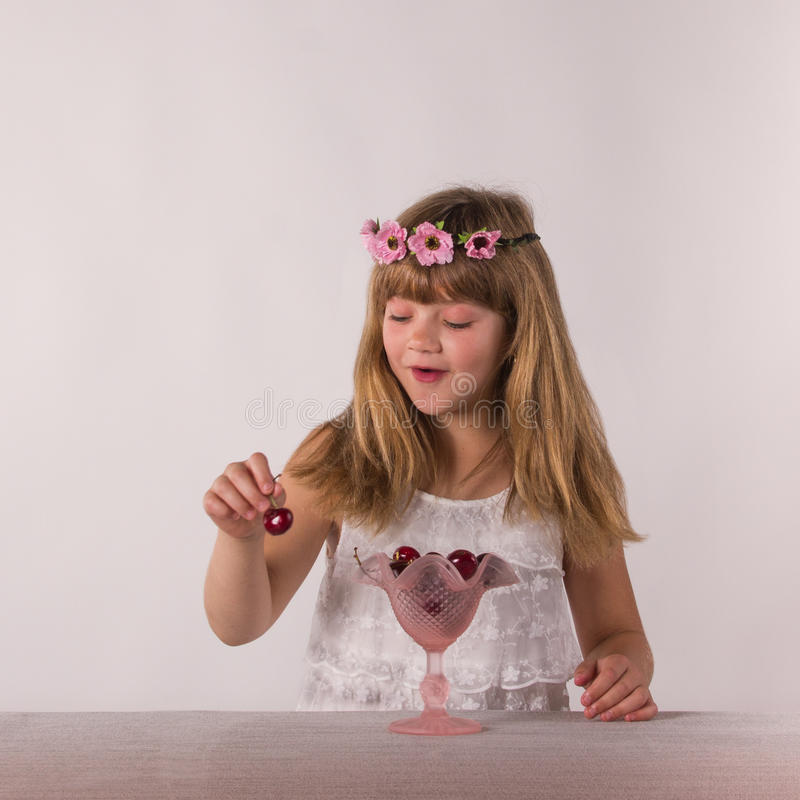 Cute brunette little girl eating gladly a big cherries. Cute brunette little girl eating with great relish a big cherries royalty free stock photo