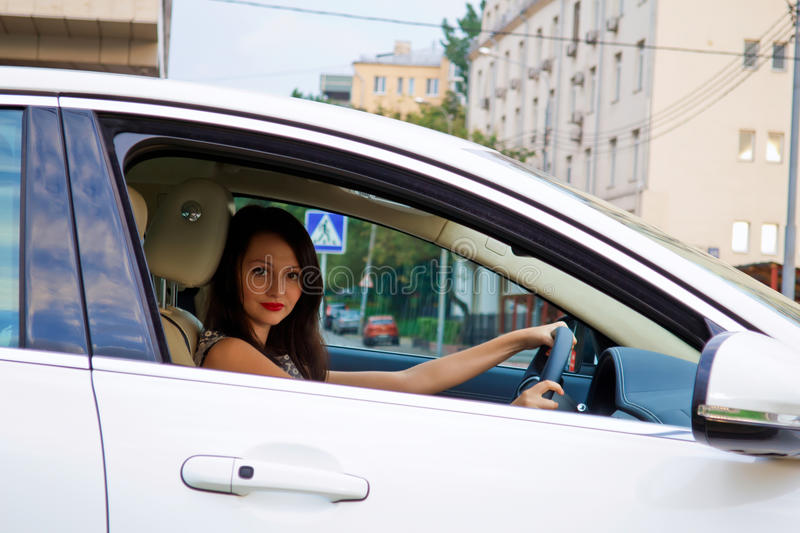 Cute brunette and luxury car. Cute brunette with red lips in the luxury white car (Jaguar XF) outdoor. Driving. Inside car stock photography