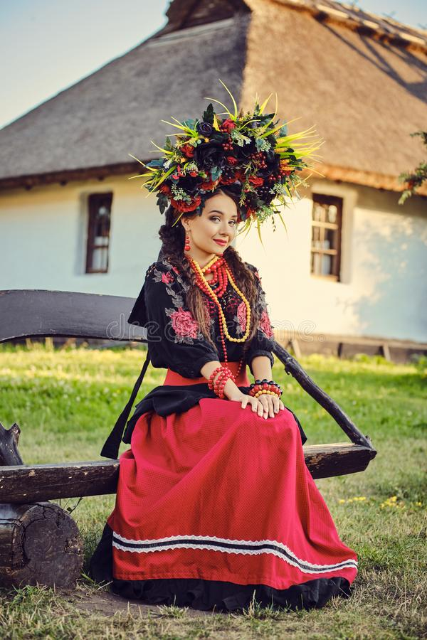 Brunette girl in a white ukrainian authentic national costume and a wreath of flowers is posing sitting on a wooden. Cute brunette maiden with a long dark hair stock photo